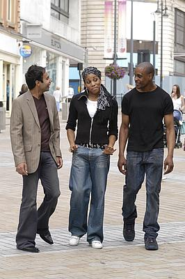 Asian male, black female and black male talking in the street.