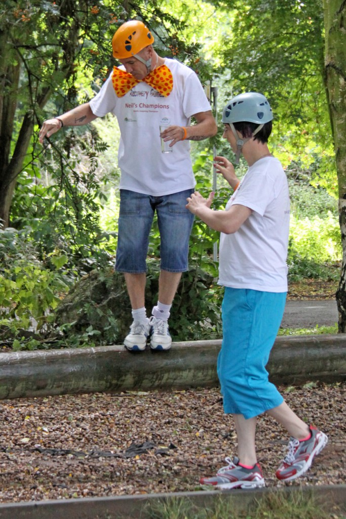 Two people helping each other walking on a log