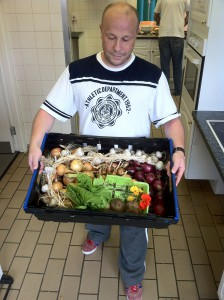 man holding box of vegetables