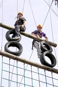 Two people climbing on an assault course