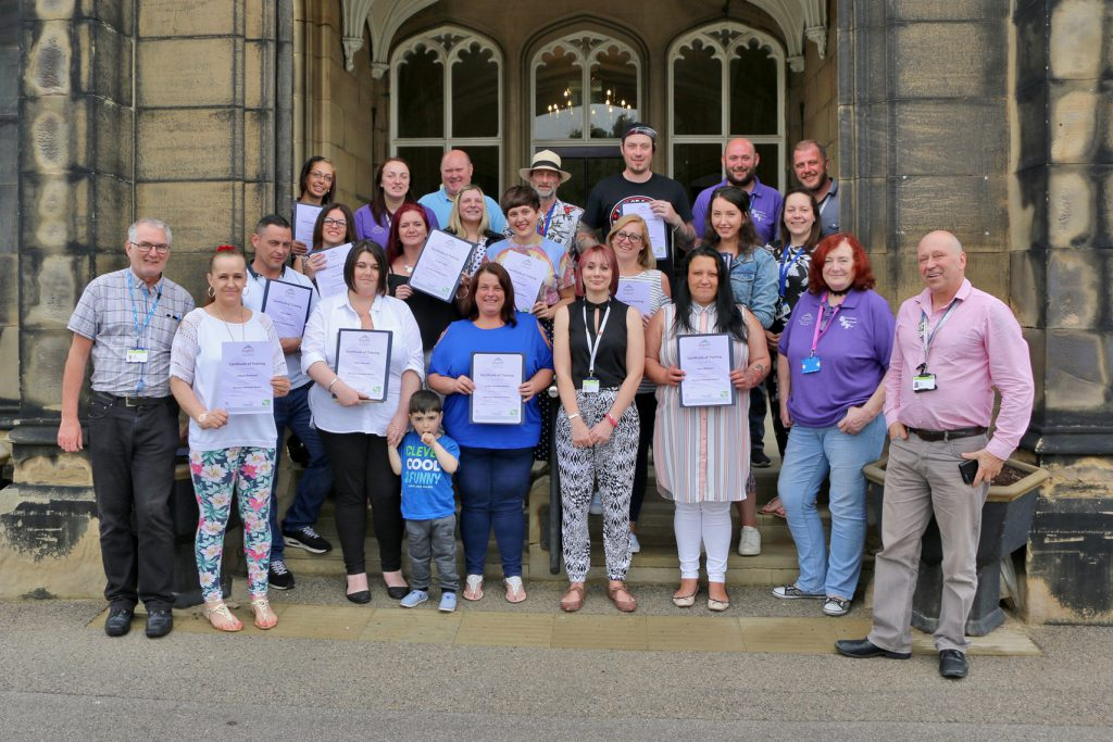 Aspire volunteer peer mentors pictured with staff and family members at the graduation event in Balby.