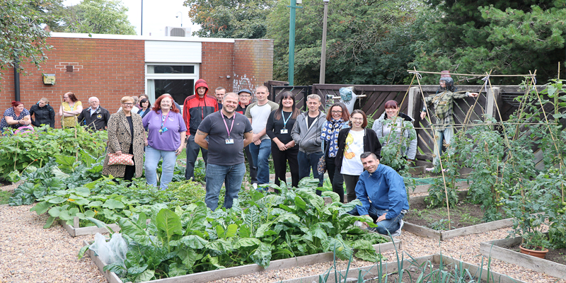 Neil Firbank (centre) with clients, volunteers, staff and their family and friends visiting the allotment